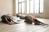 Group of young people practicing yoga lesson, doing Balasana exercise