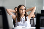 Young girl relaxing leaning back in chair, having break at workplace