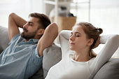 Close up of mindful couple relaxing on sofa at home