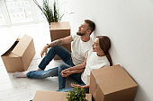 Tired couple sitting leaning back against wall in new apartment