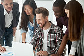 Happy multi-ethnic team excited by online result looking at laptop