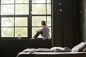 Lonely sad young woman sitting on windowsill at home
