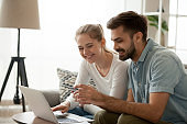 Happy couple purchasing online holding credit card