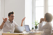Diverse excited male and female colleagues happy about online win