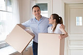 Excited couple holding cardboard boxes entering own house