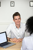 Confident male millennial applicant smiling at job interview, vertical view