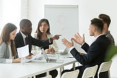 African worker disputing disagreeing with caucasian colleague during team meeting
