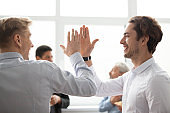 Smiling male colleagues giving high five in office celebrating victory