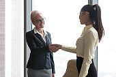 Smiling mature businesswoman handshake young employee congratulating with success