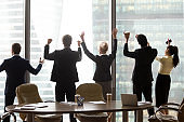 Excited office workers stand near window rising hands celebrating success
