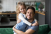 Portrait of happy dad hugging kid daughter looking at camera