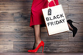 Legs of woman in red dress and shopping bag