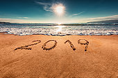 Happy New Year 2019 lettering on the beach. Sea sunrise.