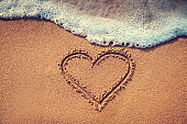 Drawing heart on the sand. Summer love background.