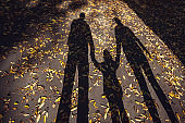 Shadows of a family with father, little kid and pregnant mother in sunset on the road with autumn leaves