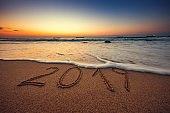 Happy New Year 2019 concept, lettering on the beach during Sea sunrise.