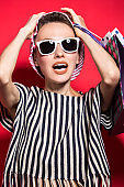 Crazy shopping woman  with shopping bags over bright red background