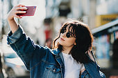 Portrait of an amazing short haired girl with sunglasses dressed in blue jeans jacket and doing selfie in the street with a red smartphone.
