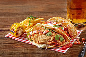 Chicken fajitas with grilled onions and bell peppers and serve with flour tortillas, corn grilled and french fries on wooden background