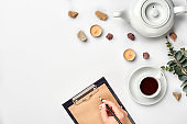 A woman hands writing on empty book note, diary, spread mockup, top view, studio. Cup of coffee break