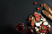 Prosciutto, salami, baguette slices, tomatoes and nutson rustic wooden board, two glasses of red wine over black background