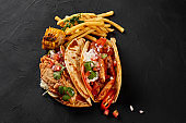 Chicken fajitas with grilled onions and bell peppers and serve with flour tortillas, corn grilled and french fries on black background. Top view