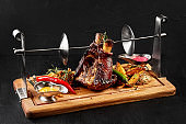 Roasted pork knuckle eisbein with braised boiled cabbage, potatoes, chili peppers and mustard on wooden cutting board, on a black background