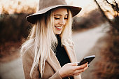Attractive young woman in elegant hat cheerfully smiling and using smartphone while standing on blurred background of autumn countryside.Cheerful lady browsing smartphone in nature