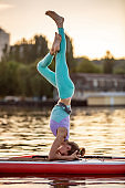 Sporty woman in yoga position on paddleboard, doing yoga on sup board, exercise for flexibility and stretching of muscles