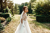 The beautiful bride in a white poses in the park