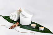 Skin care beauty treatment with jar of body moisturizer. White body lotion with big green leaf on light background