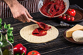 A male hand spreading tomato puree on a pizza base with spoon on an old wooden background