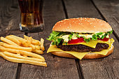 Fast food. Cheeseburger and french fries on a wooden background