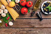 Pasta and ingredients on wooden background with copy space. Top view. Vegetarian food, healthy or cooking concept
