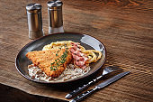Chicken schnitzel with herb, mashed potatoes and mushrooms sauce on plate on wooden table background. Healthy food