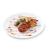 Grilled steak, baked potatoes, green basil and sauce on white plate