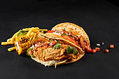 Tacos with chicken, tomato and fresh vegetables and tartar sauce on black background