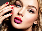 Gorgeous woman with  curly beautiful hair. Makeup. Bright colored lips.