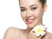 Beautiful face of cheerful  woman with flower near face