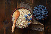 A healthy breakfast on a dark wooden background: Oatmeal and blueberries. Top view
