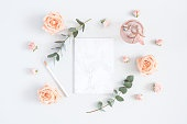 Paper blank, rose flowers, eucalyptus branches. Flat lay, top view