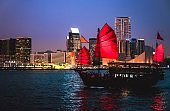 Hong Kong Victoria Harbor night view with junk boat on foreground