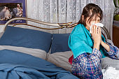 Getting Sick - a woman is lying in bed tired