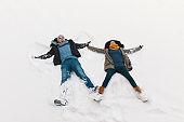 Winter holiday concept - man and woman lying happy on white snow