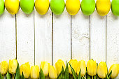 Easter background with tulips and eggs on wooden table