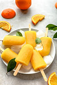 Orange popsicles with ice and juice, summer refreshing food