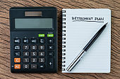 Retirement planning concept, calculator with empty notepad with pen and handwriting underline headline as Retirement Plan on wood table, plan of saving and investment for expense after retire life