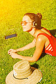 happy young brunette woman listening to the music outdoor on a summer day