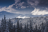 Winter Landscape in mountains. High mountains in clouds. Dramatic sky.
