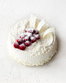 Delicious cheesecakes with cranberries, cherries, coconut flakes and white chocolate on light concrete background. Copyspace